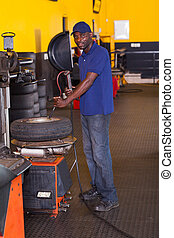 tyre shop worker inflating a trye