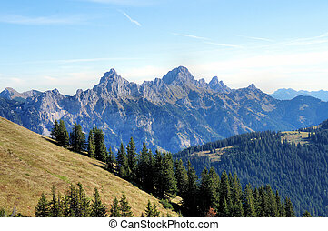 Mountain world in Tyrol, Austria; mountains, rugged rocks, valleys and mats, blue sky with white clouds