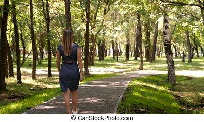uśmiecha się, pieszy, kobieta, tryb, miasto, młody, wstecz, aparat fotograficzny., dobry, idzie, przechadzki, ścieżka, dziewczyna, park.