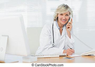 uśmiechanie się, doktor, z, komputer, używając, telefon, na, medyczne biuro