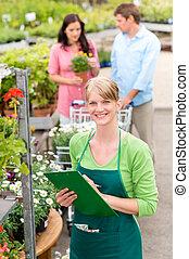 uśmiechanie się, kwiaciarka, kobieta, na, ogrodowy środek, inwentarz