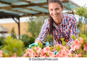 uśmiechanie się, kwiaciarka, pracujący, w, ogrodowy środek