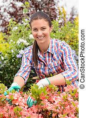 uśmiechanie się, kwiaciarka, rozmieszczające kwiecie, w, ogrodowy środek