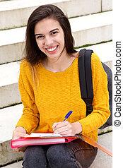 uśmiechanie się, młoda kobieta, posiedzenie na kroczy, na, uniwersytet