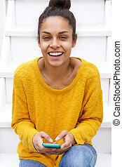uśmiechanie się, młoda kobieta, posiedzenie na schodkach, z, cellphone