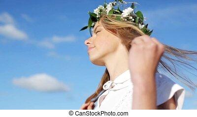 uśmiechanie się, młoda kobieta, w, wieniec, od, kwiaty