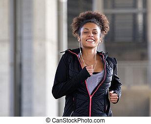 uśmiechanie się, młoda kobieta, wyścigi, outdoors, z, earphones
