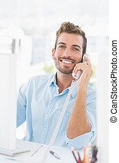 uśmiechanie się, młody mężczyzna, używając, telefon, i, komputer