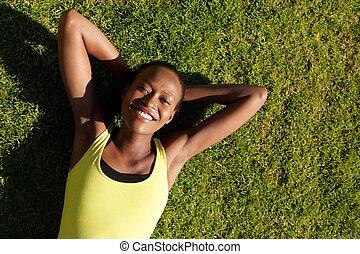 uśmiechanie się, młody, ma na sobie kobietę, odprężając, na, trawa