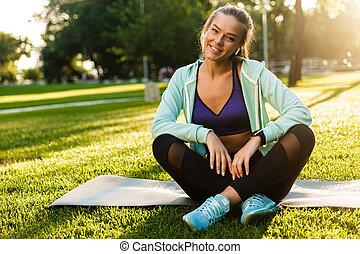 uśmiechanie się, młody, ma na sobie kobietę, w parku, outdoors, słuchający, music.