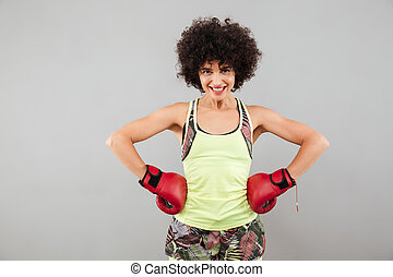 uśmiechanie się, ma na sobie kobietę, w, boks rękawiczki, dzierżawa herb, na, biodra