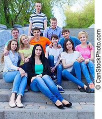 uśmiechanie się, outdoors, grupa, nastolatki, posiedzenie