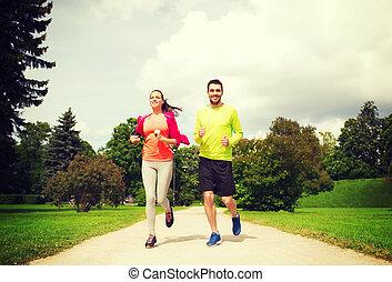 uśmiechanie się, para, z, earphones, wyścigi, outdoors