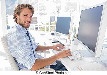 uśmiechanie się, projektant, pracujący, jego, biurko
