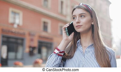 uśmiechanie się, włosy, szykowny, dziewczyna, kapitałka, młody, powołanie, telefon, brązowy, chodząc, smartphone, reputacja, koszula, pasiasty, mówiąc, miasto, wykręcanie, ulica., liczba, pociągający