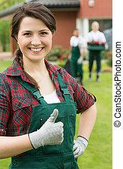 uśmiechnięta kobieta, kciuk, ogrodnik, do góry