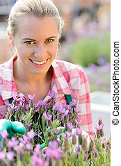 uśmiechnięta kobieta, z, purpurowy kwiat, ogrodowy środek
