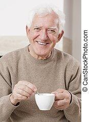 uśmiechnięty człowiek, pijąca kawa