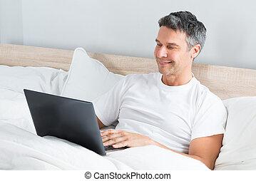 używający laptop, łóżko, odprężając, człowiek