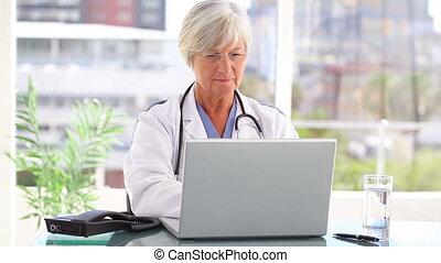 używający laptop, dojrzały doktor