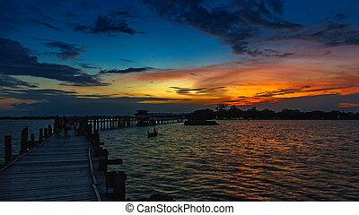 U-Bein Bridge. - Sunset with silhouettes of people on Bridge...