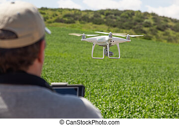 UAV Drone Pilot Flying and Gathering Data Over Country Farm Land.