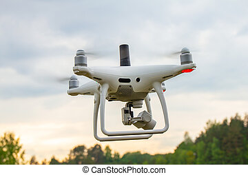 UAV White drone Quadr copter in flight with geodesic module and digital camera explores the area on the background of a sunset with clouds. The copter in the air take aerial photo in the blue sky