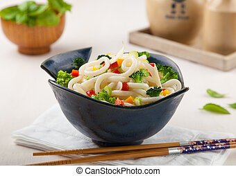 Udon, Japanese noodles with vegetables in a handmade ceramic bowl.
