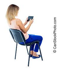 udsigt tilbage, i, kvinde sidde stol, og, kigge hos, den, skærm, i, den, tablet.