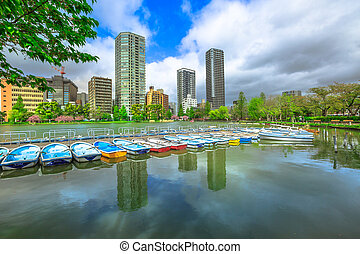 Pedal boats and Tokyo skyscrapers reflecting on Shinobazu Pond in Ueno Park, a public park next to Ueno Station in central Tokyo. Ueno Park is considered the best in Tokyo for cherry blossoms.
