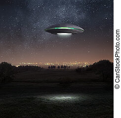 Ufo at night - Alien spacecraft is hovering abpve the meadow