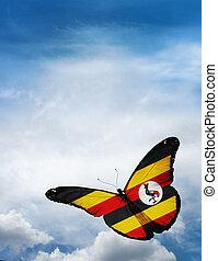 Uganda flag butterfly flying on sky background