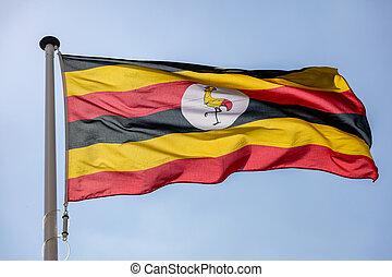 Uganda flag waving against clear blue sky