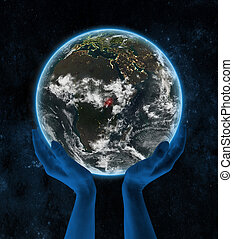 Uganda on night planet Earth in hands