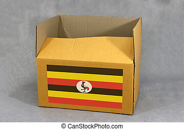 Ugandian flag on brown carton box, Paper packaging for put products. The concept of Uganda export trading.