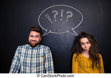 Ugly couple grimacing over chalkboard background