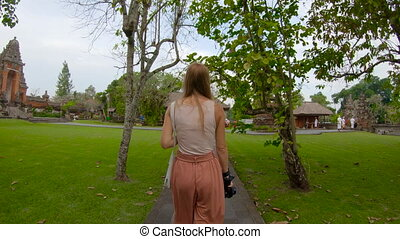 UHD slowmotion shot of a young woman walking in the Taman...