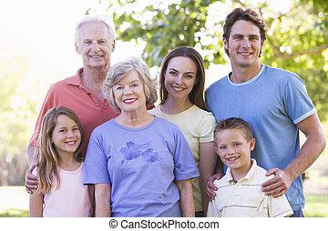 uitgebreide familie, staand, in park, het glimlachen