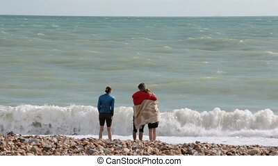 UK, Brighton. Three young students are on the shore of Atlantic ocean. Friends wet their feet in the surf. The seagulls are walking on the foreground.