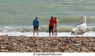 UK, Brighton. Young couple and a girl are on the shore of Atlantic ocean. A couple is hugging, a girl is standing side by side. The seagulls are walking on the foreground.