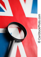 UK flag looking through a magnifying glass. Total surveillance of the country of England. The concept of hidden threats and control over the country