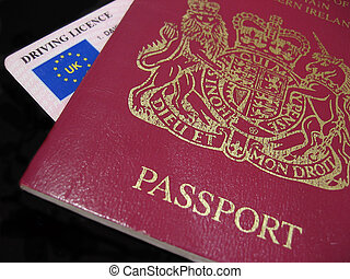 UK Passport and drivers licnense in close-up against a dark background