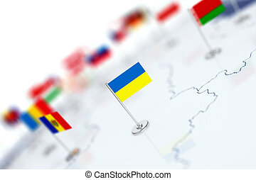 Ukraine flag in the focus. Europe map with countries flags