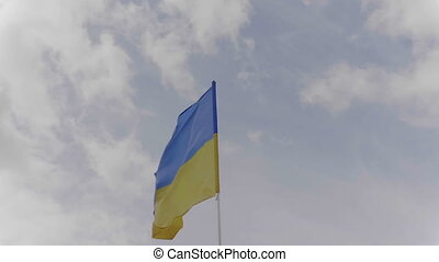 Ukraine flag on the flagpole waving in the wind against a...