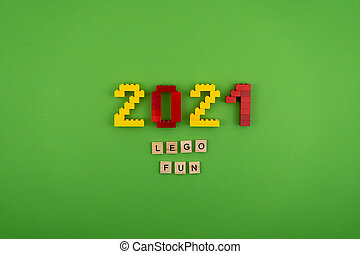 Ukraine, Kyiv - September 20, 2020: The word LEGO 2021 is lined with wooden letters on a green background. Figures from the constructor top view. Postcard in place for text. Flatlay. Yellow and red numbers. The words.