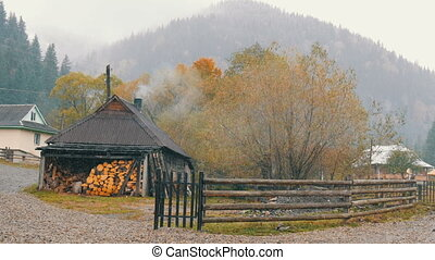 Ukraine, the highest mountain village of the Carpathians, Dzembronya. The first snow in October. A wooden house is heated with firewood. Smoke comes from the chimney