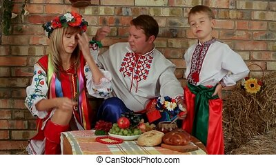 Ukrainian family sits around the dinner table. Historical period.