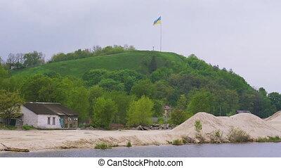 Ukrainian flag fluttering over Devich Mountain in Trypillia...