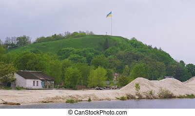 Ukrainian flag fluttering over Devich Mountain in Trypillia...