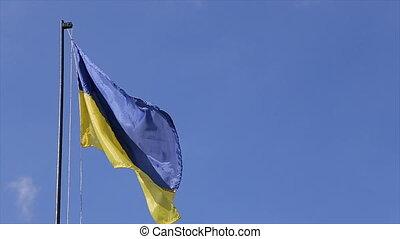 Ukrainian national flag against the blue sky. Close up